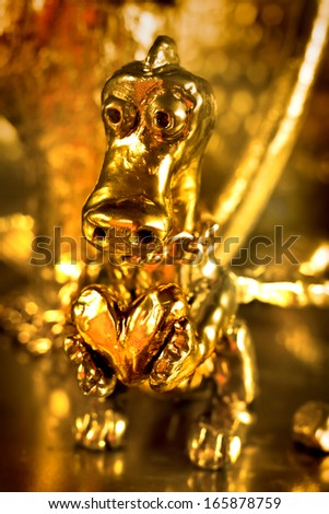 Golden Dragon with a heart on gold background - stock photo