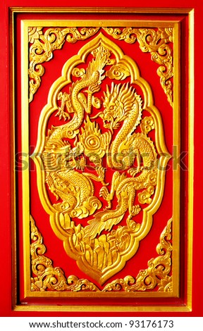 Golden dragon wood carved on red wall - stock photo