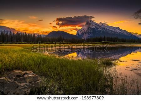 Golden early fall sunrise over the Canadian Rockies and Vermilion Lakes on the outskirts of Banff, Canada - stock photo