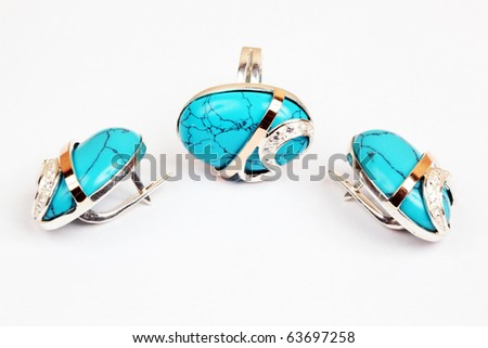 Golden earrings and ring with turquoise isolated the white background - stock photo