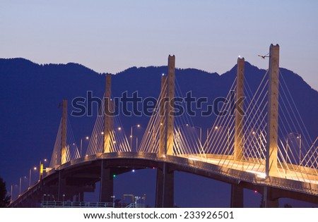 Golden Ears Bridge lit up at night. Coast Mountains behind. - stock photo