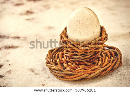 Golden easter egg in nest on vintage marmur background. background with selective focus and diffused natural light. A different type of concept image for Easter or pension financial investments.  - stock photo