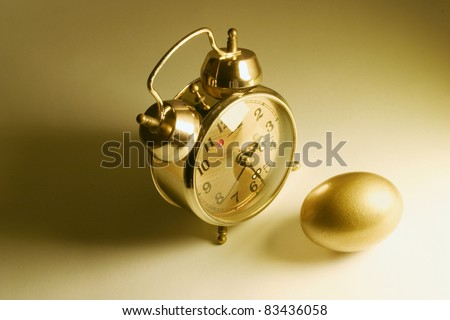 Golden Egg and Alarm Clock in Warm Tone - stock photo