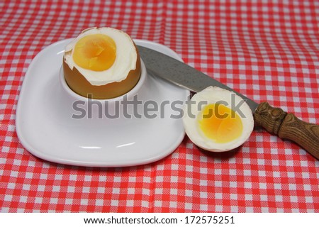 golden egg in an egg cup on a red patterned napkin - stock photo