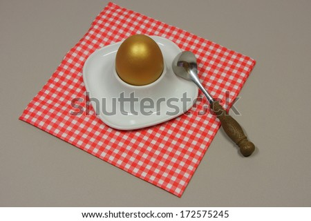 golden egg in an egg cup on a red patterned napkin with spoon - stock photo