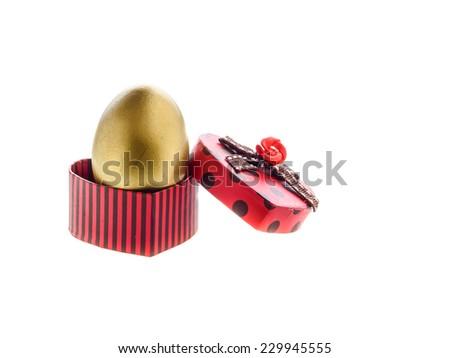 Golden egg in red gift box heart shape. - stock photo