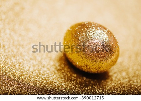 Golden egg on n shiny gold background. Macro. - stock photo