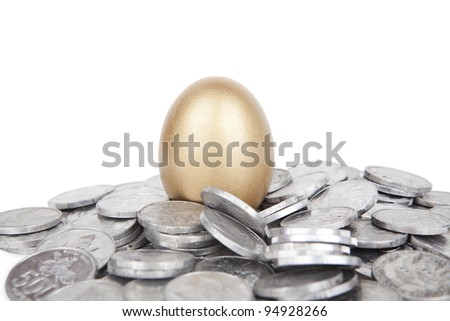 Golden egg with coins on white background - stock photo