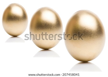 Golden eggs from small to large isolated on a white background. Concept of financial growth - stock photo
