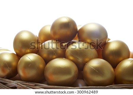 golden eggs in a basket on white background  - stock photo