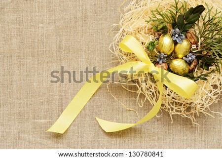 Golden eggs in the nest on a canvas background - stock photo