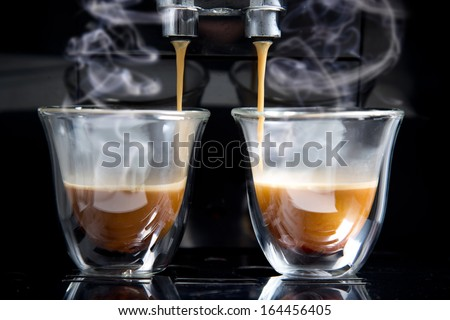 golden espresso flowing into the cups - stock photo