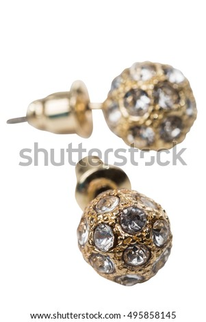 Golden ethnic earrings on white cloth as a background with clipping path