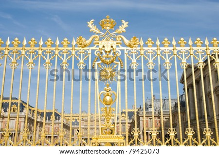 Golden fence and Versailles plalace. The Palace Versilles is a royal chateau in Versailles City paris, France. It was added to the UNESCO list of World Heritage Sites in 1979. - stock photo