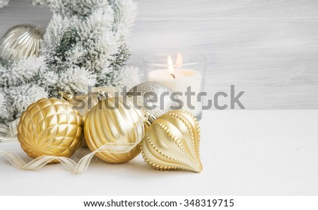 Golden Festive Globes and Ribbon for Christmas Tree, Scent Burning Candle and Snowy Wreath - stock photo