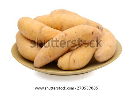 golden fingerling potatoes on plate isolated on white  - stock photo