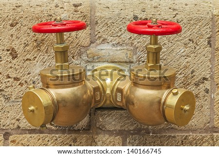 Golden Fire Hydrant on the Sand Stone Wall - stock photo