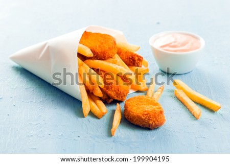 Golden fish nuggets with fried potato chips or French fries spilling out of a takeaway paper cone onto a blue surface with a small bowl of mayo dip - stock photo