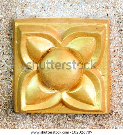 Golden flower statue on the temple wall. - stock photo