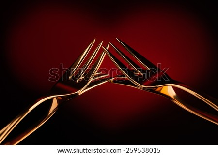 Golden forks with red heart shape on background - stock photo
