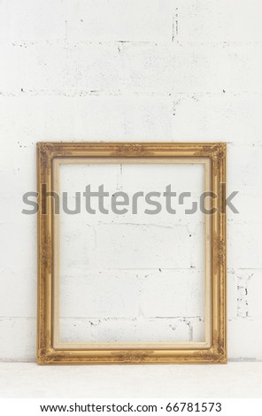 golden frame on white brick wall - stock photo