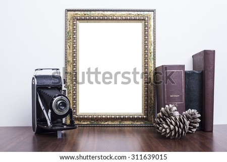 Golden Frame with old books and old camera on wood table - stock photo