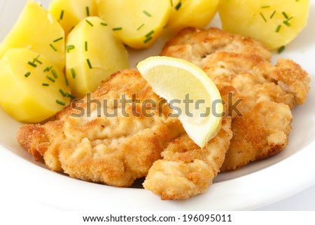 Golden fried schnitzel with boiled potatoes, chives and a slice of lemon. - stock photo