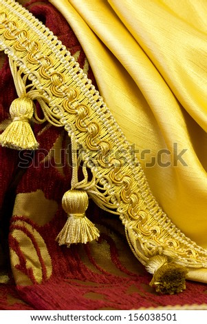 golden fringe on the background of curtain fabrics - stock photo