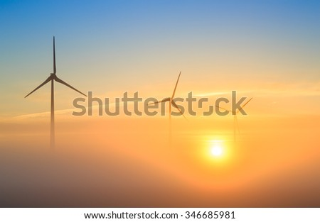 Golden future for wind energy: wind turbines generating sustainable energy during a foggy sunrise. - stock photo