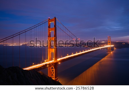 Golden Gate Bridge after a spring storm glows against the background of San Francisco skyline, shot from Battery Spencer (Marin Headlands) at dusk. - stock photo