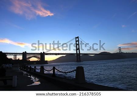 Golden Gate Bridge along the San Francisco Bay during sunset - stock photo