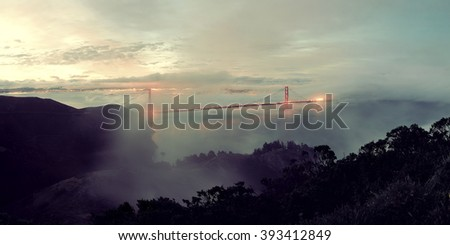 Golden Gate Bridge and fog in San Francisco viewed from mountain top - stock photo