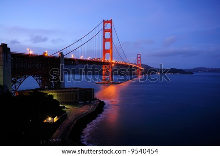 Golden Gate Bridge and Fort Point overlook glow in the dusk after a winter storm - landscape orientation. - stock photo