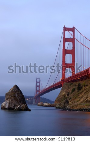 Golden Gate bridge as seen from Fort Mason, Sausalito is glowing in the cold bluish San Francisco Bay Area pre-dawn fog. - stock photo
