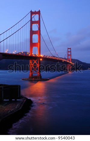 Golden Gate Bridge as seen from Fort Point overlook is glowing in the dusk after a winter storm - stock photo