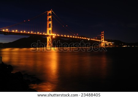 Golden Gate Bridge as seen from Fort Point overlook is glowing in the night against starry sky - stock photo