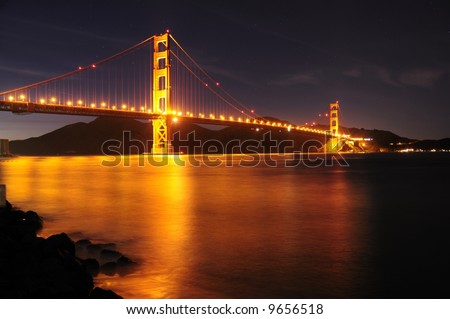Golden Gate Bridge as seen from Fort Point overlook is glowing in the night with star trails in the sky behind it