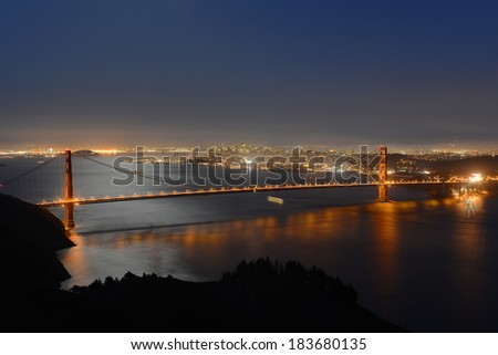 Golden Gate Bridge at night, with San Francisco city skyline at back ground, San Francisco, California, USA - stock photo