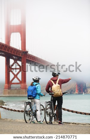 Golden gate bridge - biking couple sightseeing in San Francisco, USA. Young couple tourists on bike tour enjoying the view at the famous travel landmark in California, USA. - stock photo
