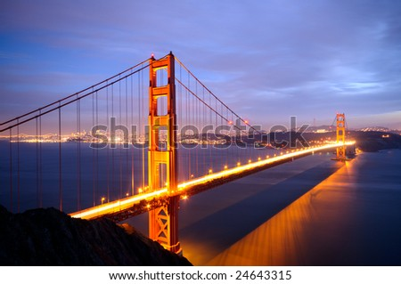 Golden Gate Bridge from Battery Spencer viewpoint glows in the dusk after a spring storm with San Francisco skyline in the background - stock photo
