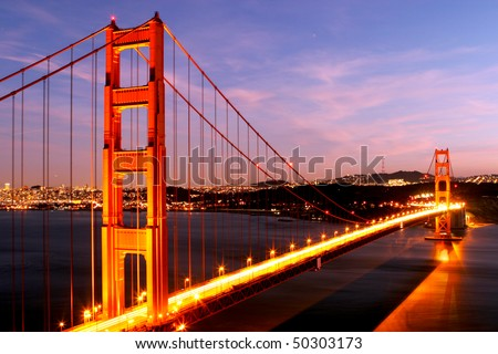 Golden Gate Bridge glowing at night - stock photo