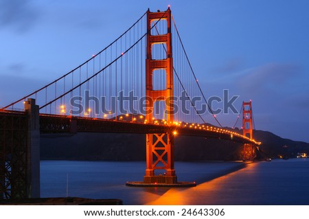 Golden Gate Bridge glows after a spring storm. Shot at dusk from Fort Point viewpoint. Landscape (horizontal) orientation. - stock photo