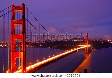 Golden Gate Bridge glows in the dusk - as seen from the vista point on a Lonely Tree Hill over Highway 101 with San Francisco skyline and Twin Peaks TV tower in the background.