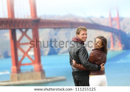 Golden gate bridge happy travel couple in San Francisco, USA smiling at camera. Young interracial hipster couple enjoying the view at the famous travel landmark. - stock photo