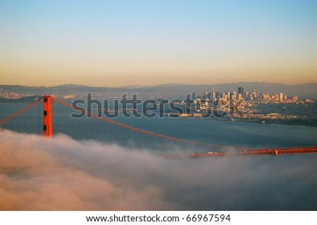 Golden Gate Bridge in fog in a winter dusk, with San Fransisco in the back ground. - stock photo
