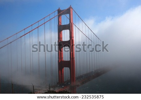 Golden Gate Bridge in fog with a blue sky overhead.