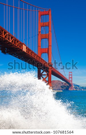 Golden Gate Bridge in San Francisco with big wave splash and spray in the foreground
