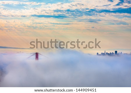 Golden Gate Bridge in thick fog and outline of San Francisco after Sunrise - stock photo