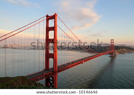 Golden Gate Bridge lit by the setting sun against the background of San Francisco skyline and beautiful cloudy sky - stock photo
