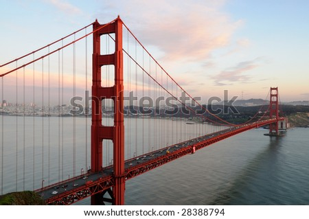 Golden Gate Bridge lit by the setting sun against the background of San Francisco skyline and beautiful cloudy sky. Shot from Battery Spencer, Marin Headlands - stock photo